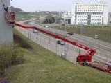 Pronájem plošiny Brno. Zde náš zákazník ušetřil čas díky dosahu plošiny přes zaparkovaná vozidla. Na fotce je přistup z chodníku, pracovalo se i z parkovišť vedle haly.